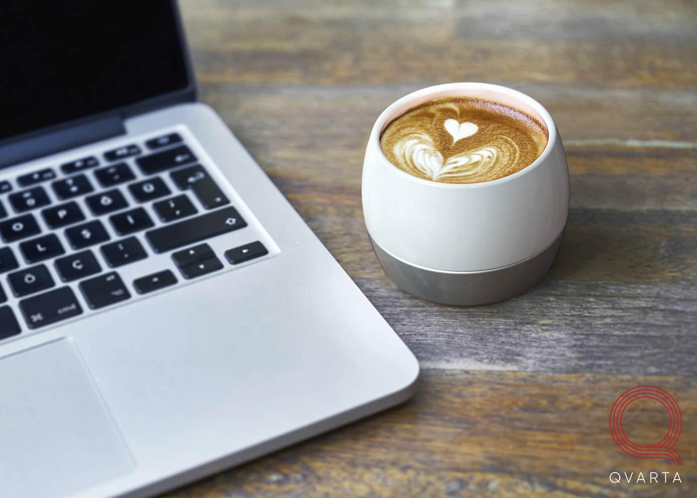 Смарт-чашка HEATLIE с кофе в интерьере возле ноутбука.