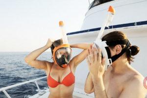 Люди одевают маску для снорклинга.