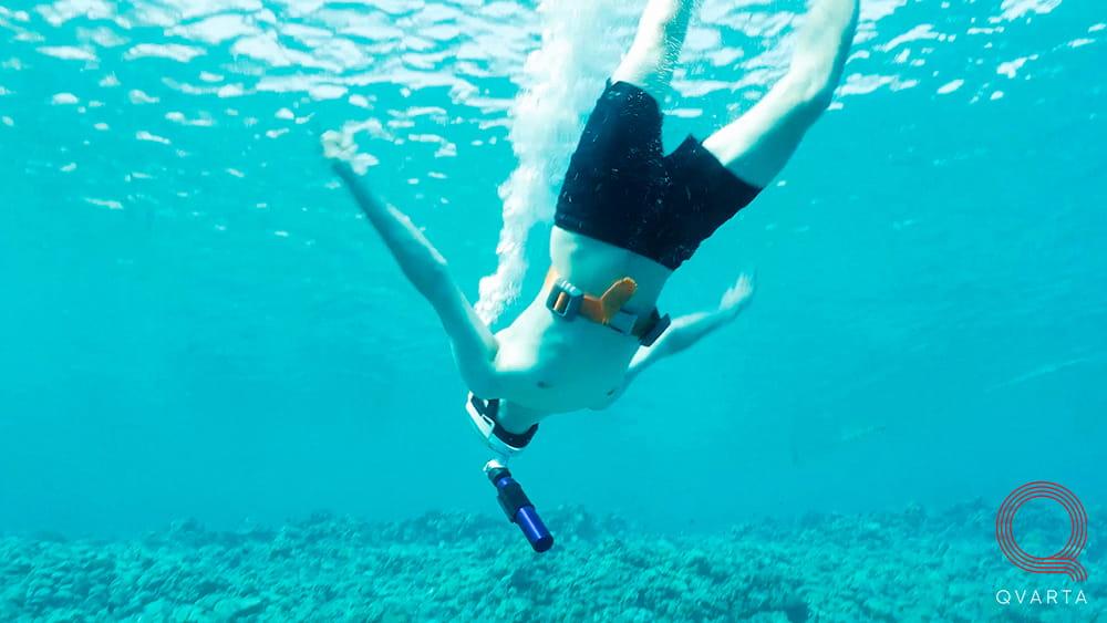 Мужчина в маске для снорклинга под водой.