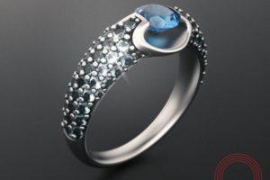 Фото кольца с лого Qvarta стоящее на столе.